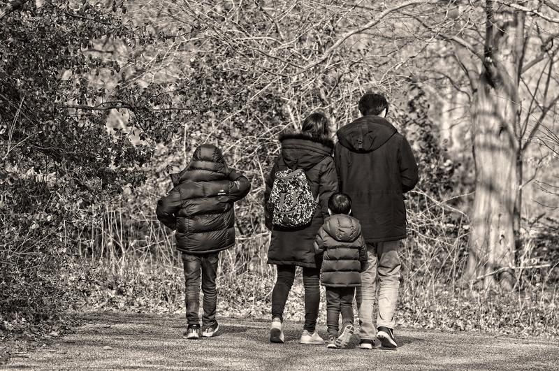 Black and white image of family walking on a trail with their coats on and it looks like the weather is chilly or cold.