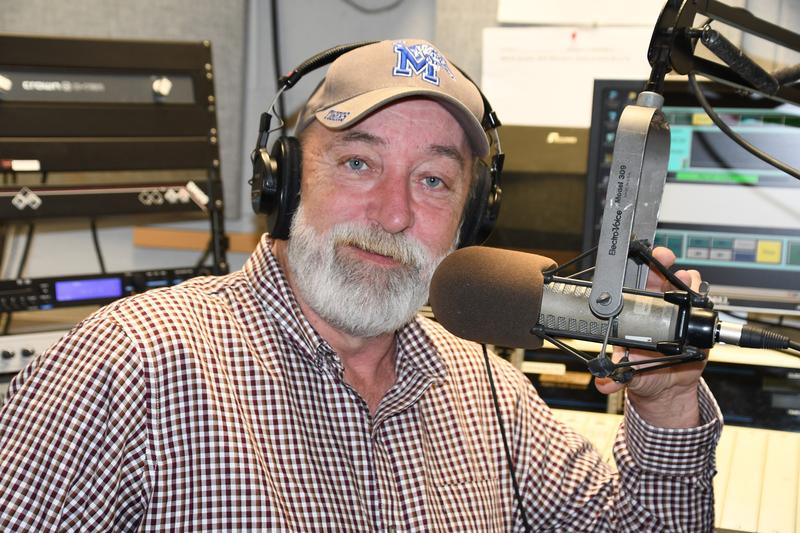 Image of a male DJ smiling, wearing a hat working in a radio studio