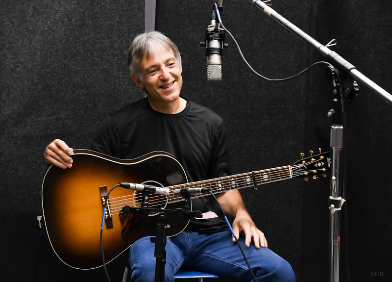image of singer songwriter Chuck Brodsky sitting, smiling and holding guitar