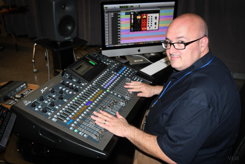 image of man working in sound studio mixing music on console or borad