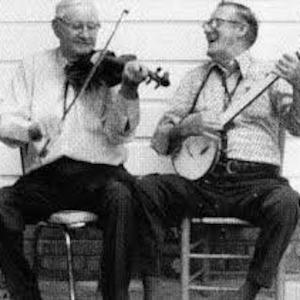 Two men playing instruments and smiling