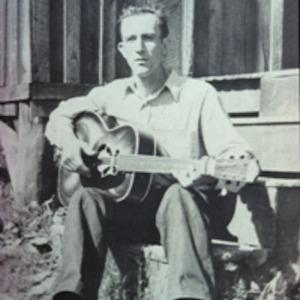 Frank Proffitt playing guitar while sitting outside