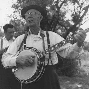 Man standing and playing banjo while singing