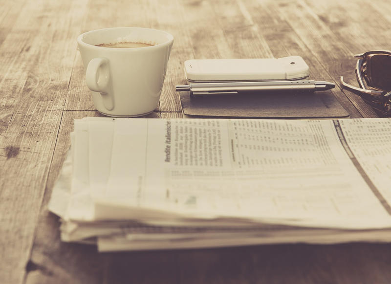 image of newspaper with coffee cup, cell phone and glasses