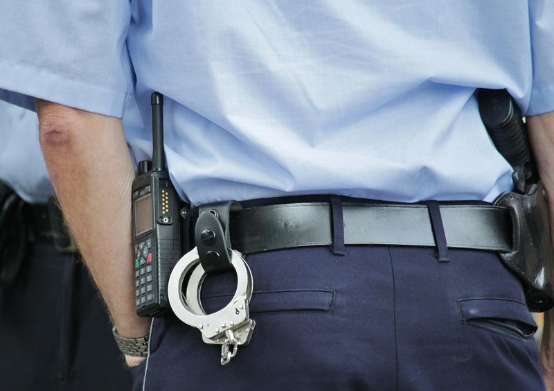 image of police officers with handcuffs attached to belt