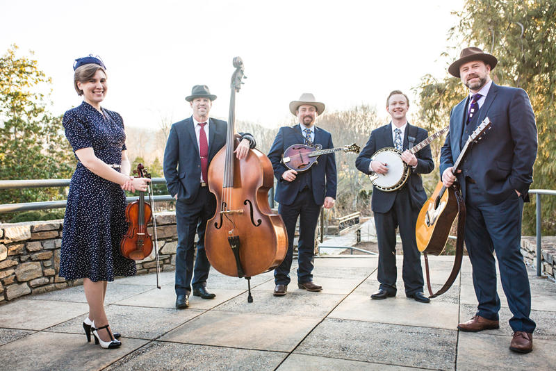 Image of bluegrass band members standing outside with instruments