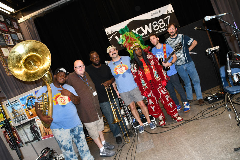 Image of a band from New Orleans with very colorful members and a giant sousaphone