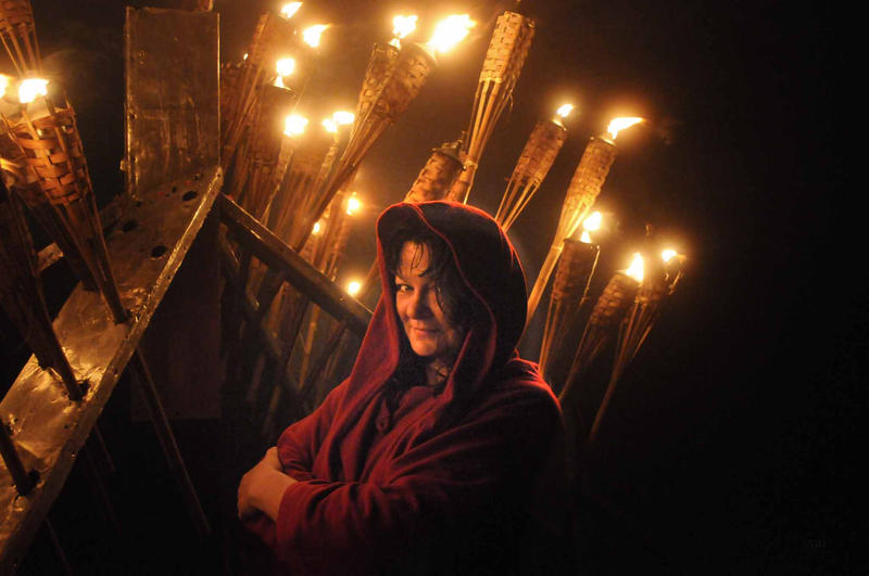 woman in Celtic wrap with torches lit behind her