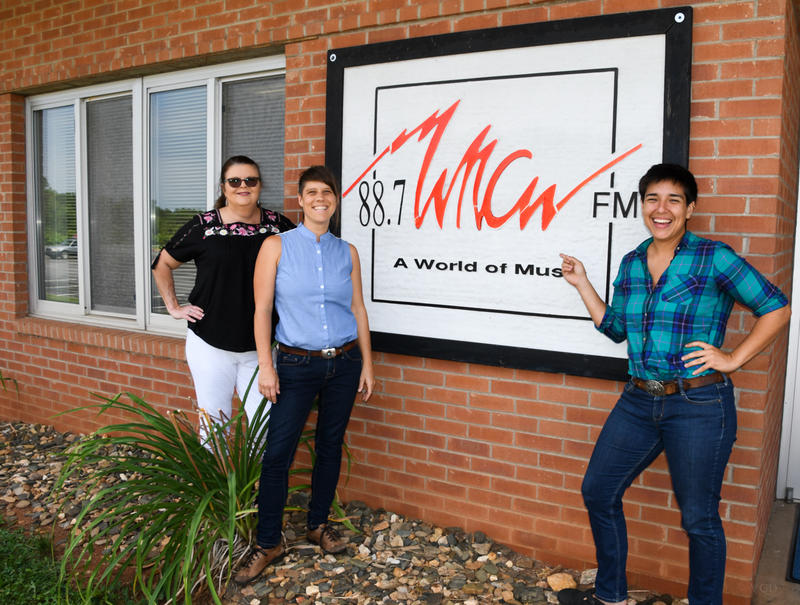 Female band members and DJ standing in front of WNCW sign