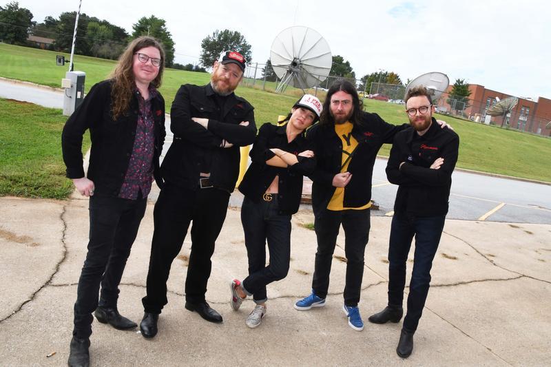 Band members posing near satellites
