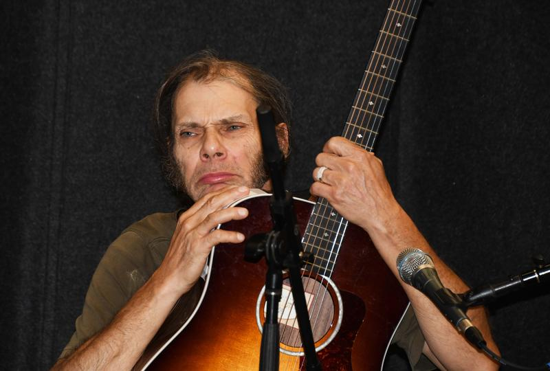 Man holding guitar looking serious and pensive