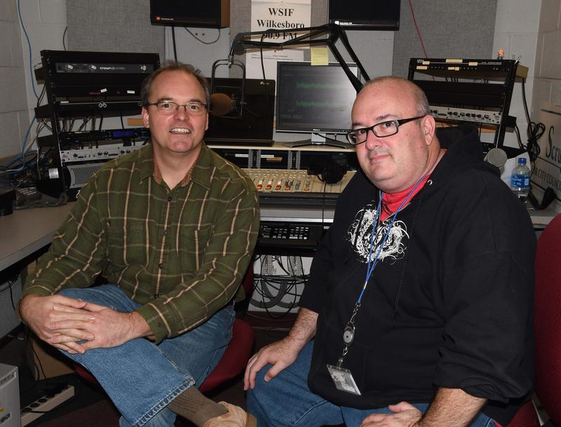Two men smiling at camera sitting in a radio production room