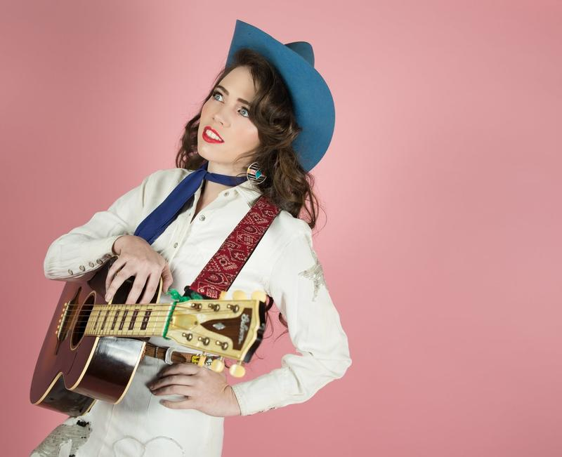 Image of woman in cowgirl outfit smiling holding guitar