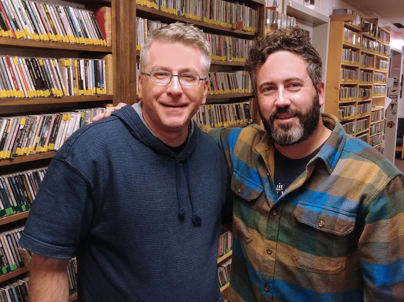Image of two men smiling and posing for camera at radio station with cds in the background