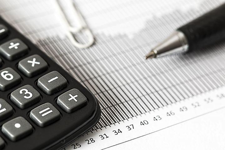Image of a calculator and pen with paper