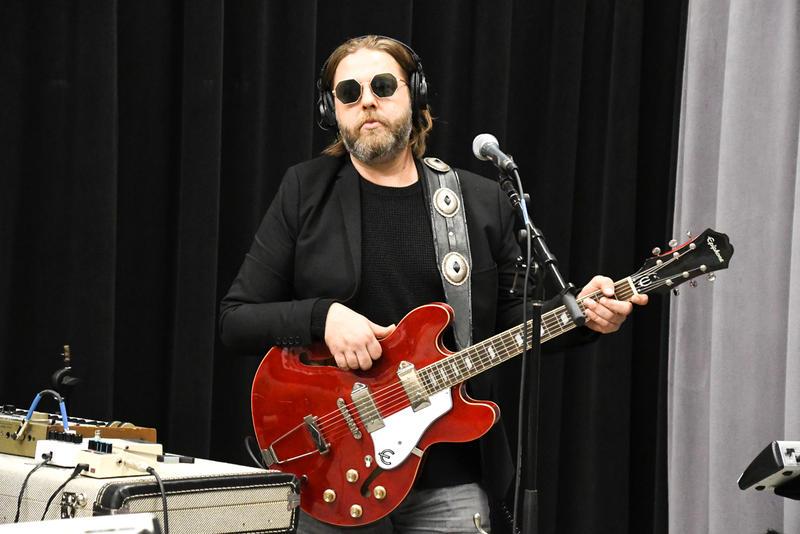 Man holding guitar wearing glasses