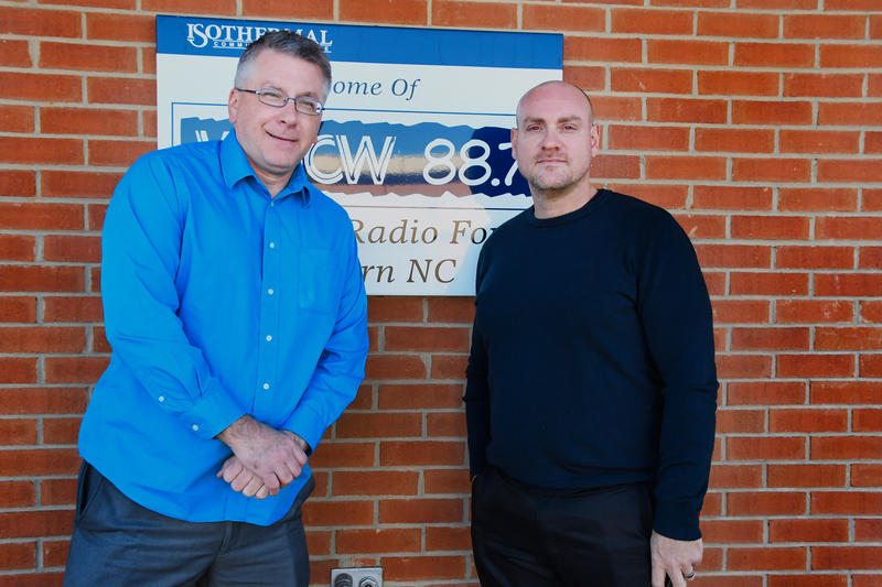 Two men posing in front of WNCW Sign at station