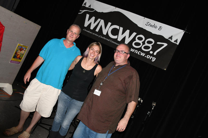a DJ, Musician and Sound Engineer posing under WNCW Banner