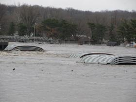 The roofs of two sunken barges rise above the Illinois River. They and two others sank the night of April 18 and are resting next to the Marseilles Dam.