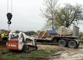 Workers move enormous rocks into place to repair the damage caused along the Illinois River by the April floods.