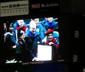 Scoreboard shot of former Governor Jim Thompson receiving his honorary degree from NIU's law school Saturday, May 25th.