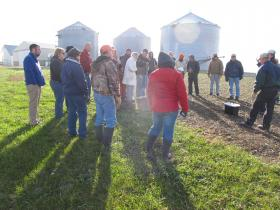 A group of farmers listens to a presentation on cover crops at the Baumgartner farm