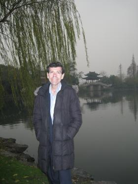 "Bill Goldenberg in front of the lake in China that inspired the piece ""Autumn Moon, Peaceful Lake"" by Chinese composer Chen Peixun"