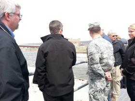 Congressman Adam Kinzinger is joined by Army Corps of Engineers officials atop the improved, but not yet finished, Marseilles Dam.