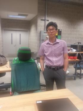 Dr. Jay Kim in the vehicle seat testing area at NIU's College of Engineering and Engineering Technology. The green mat reads sensors that gauge body movement.