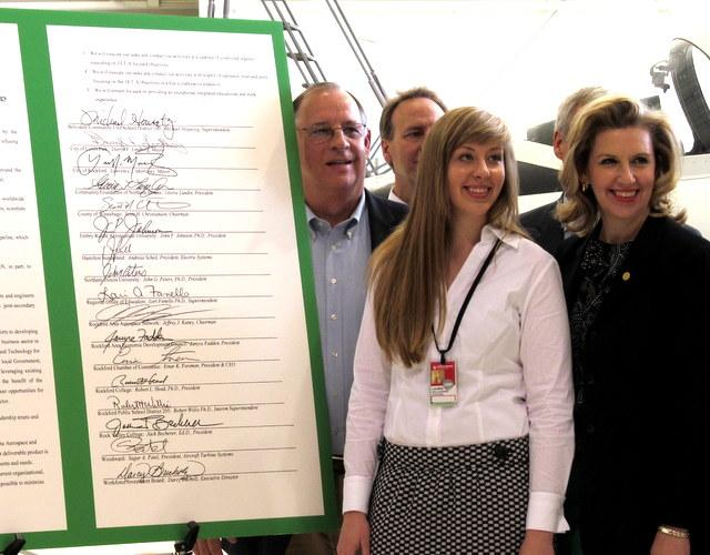 Loves Park Mayor Darryl Lindberg, NIU student Laura Gallagher, and NIU's Rena Cotsones with the signed copy of the Declaration creating the Joint Institute of Engineering and Technology - Aerospace.