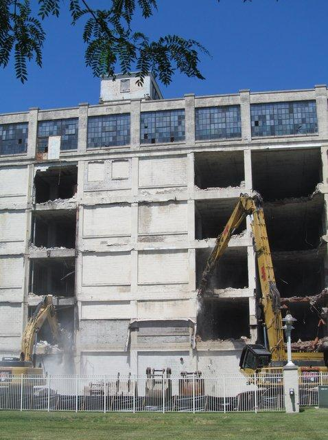 Two pieces of heavy equipment work to bring down the Tapco Building in Rockford's downtown.