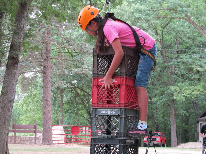 Girl scout climbing milk crates at Camp McCormick