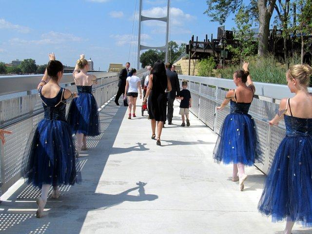Rockford Dance Company dancers escort pedestrians down the new segment of Rockford's riverfront.