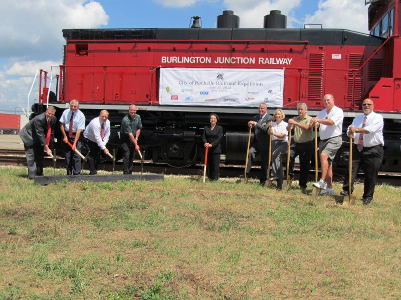 City, state and federal officials and business leaders wield hammers and shovels in a ceremony marking the start of the railroad's expansion