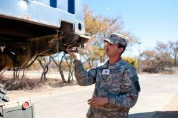 Sgt. Christopher Huitrado of Streator, Ill., automated logistical specialist with Company A, 405th Brigade Support Battalion out of Streator, locks a container into the enhanced container handling unit on duty in Botswana