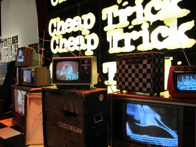 Some of Cheap Trick's live performances play on old-school televisions on a stage in the exhibit at Burpee Museum.