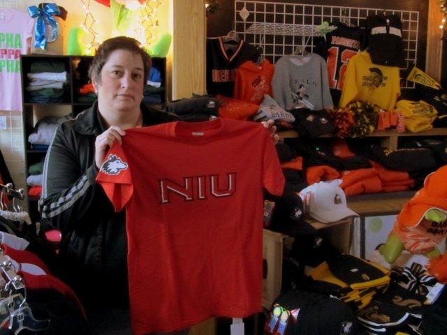 Brenda Lehan shows off her Huskie fan supplies at S.O.A.S. Apparel and Design in DeKalb