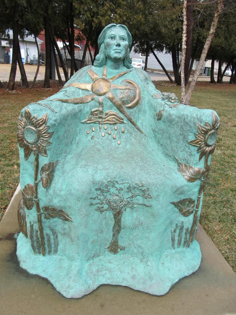 """Bountiful Bench,"" by Christina Murphy, 2008. Location: Oregon Public Library.  Inspired by the Rock River, the woman of nature holds the produce and natural bounty of the area"