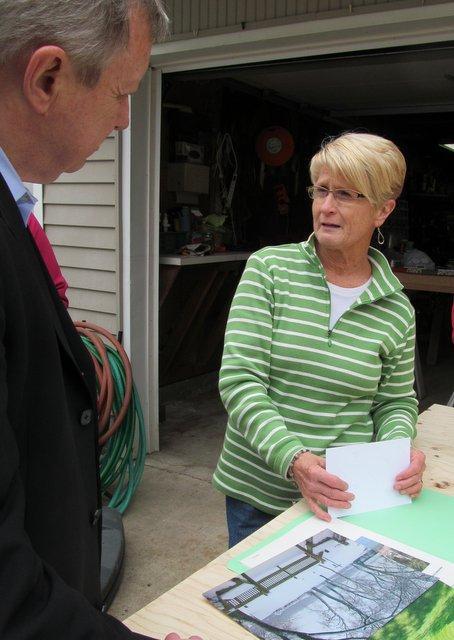 "Senator Durbin looks over ""before the flood"" photos with a homeowner"