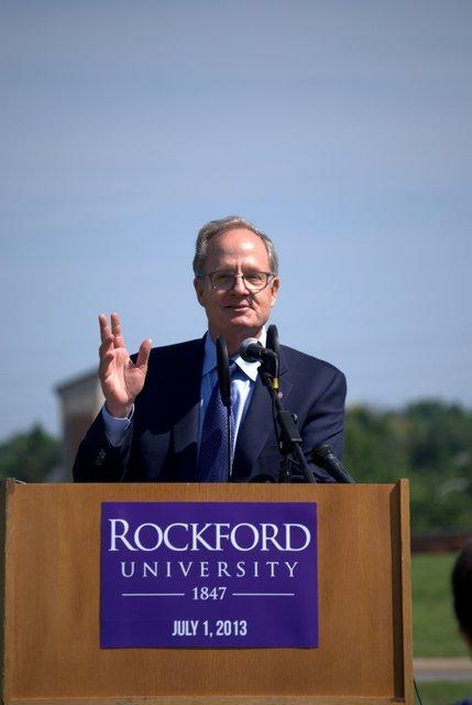 Board of Trustees Chair Charles Colman proclaims the new status as Rockford University.