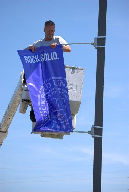 Workers change banners Monday along the entry drive at Rockford University.