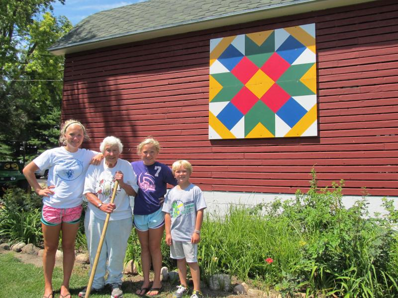 "Nancy Nienhuis stands in front of her barn quilt ""Farmer's Daughter"" with her grandchildren"