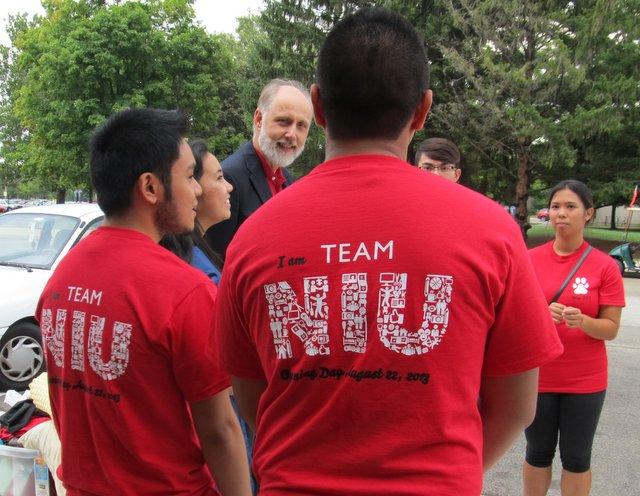 NIU President Doug Baker chats with members of the Philippine Student Association as they help other students move in.