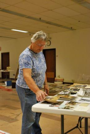 Historical Society volunteer Janet Goodell looks through old pictures salvaged from the July 15th fire