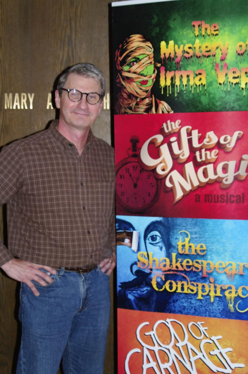Artistic Director Richard Raether poses with the season playbill for Artists' Ensemble Theatre