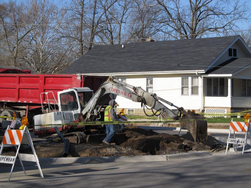 Workers excavate topsoil from a rain garden being constructed at Douglas and Simms in Aurora. The curbs have already been laid.  When construction is done, plantings will sit on a bed of rock, gravel and sand.