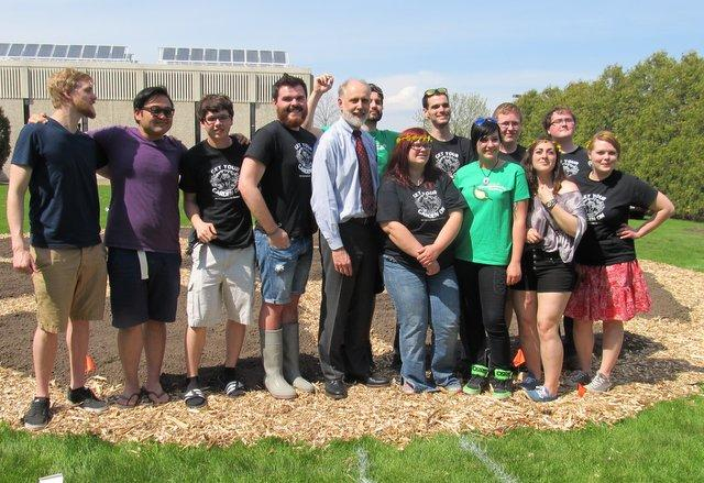 A crowd of NIU students lines up for photos with NIU President Doug Baker at the Communiversity Garden's latest project