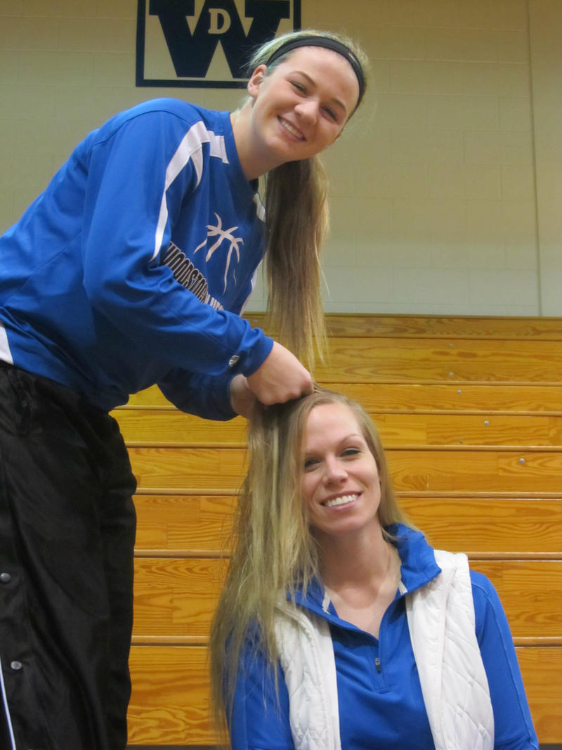 A Blue Streaks player braids coach Jennifer Nichols-Hogle's hair before a game