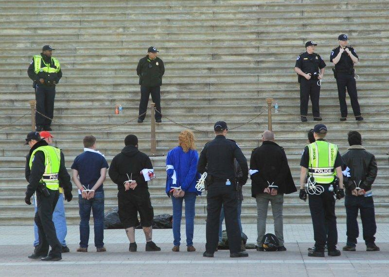 Roscoe resident Elizabeth Lindquist, center, was among more than 400 arrested for civil disobedience Monday