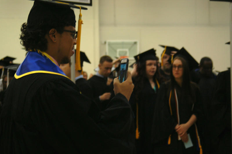 A student takes a photo for two others while waiting for graduation ceremonies to begin at Northern Illinois University Saturday.
